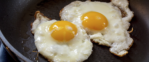 two fried eggs in a black pan